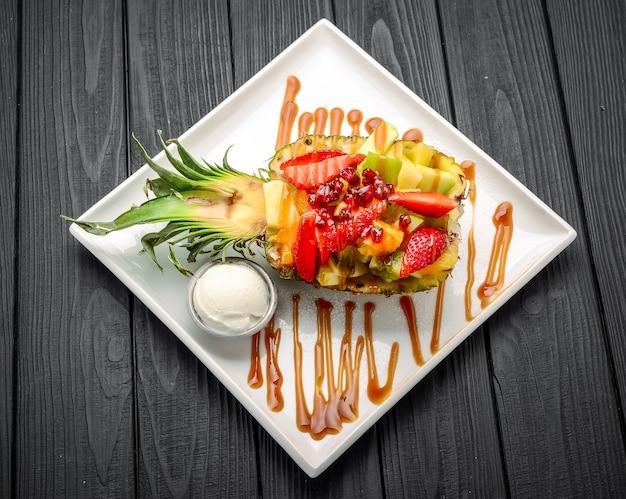 Sałatka ze świeżych owoców w ananasie przekrojonym na pół, polana karmelem