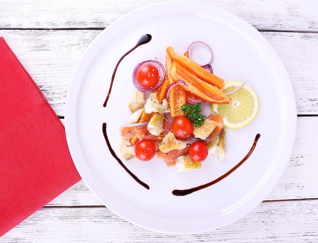 Sałatka ze świeżych ryb z warzywami na talerzu na drewnianym stole z bliska