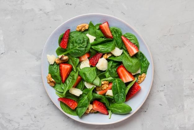 Sałatka ze świeżych truskawek z liśćmi szpinaku, parmezanem i orzechami włoskimi. zdrowa dieta