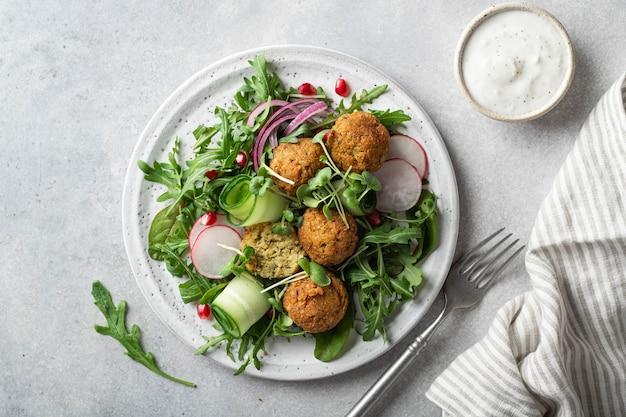 Sałatka ze świeżych warzyw i falafel na białym talerzu ceramicznym na tle betonu widok z góry