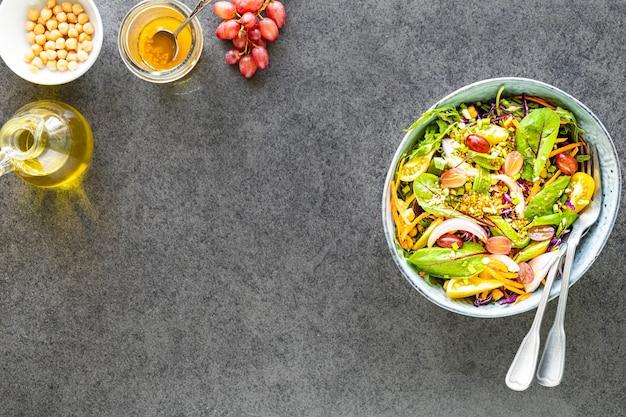 Sałatka ze świeżych warzyw i owoców w talerzu na czarnym kamieniu. widok z góry