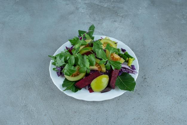Sałatka ze świeżych warzyw na białym talerzu.