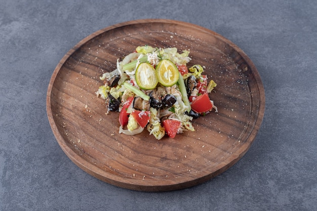 Sałatka ze świeżych warzyw na drewnianym talerzu.