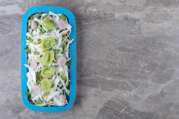 Sałatka ze świeżych warzyw na niebieskim talerzu.