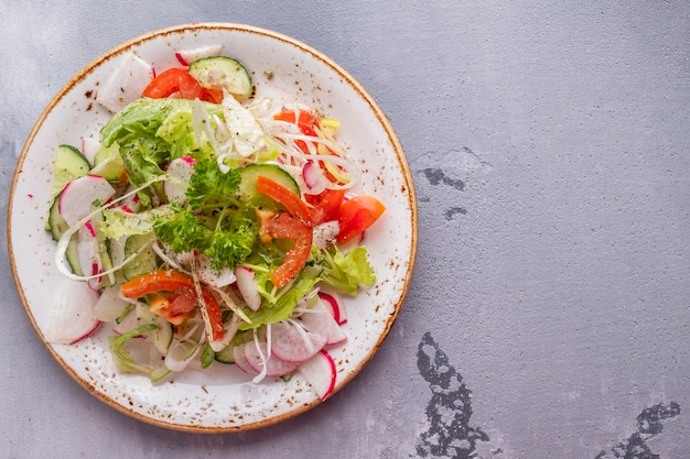 Sałatka ze świeżych warzyw oa talerz. koncepcja zdrowej żywności.