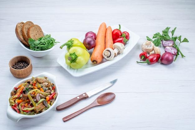 Sałatka ze świeżych warzyw pokrojona z mięsem wraz z bochenkami chleba i całymi warzywami i zieleniną na lekkim biurku, witamina sałatka z posiłków spożywczych