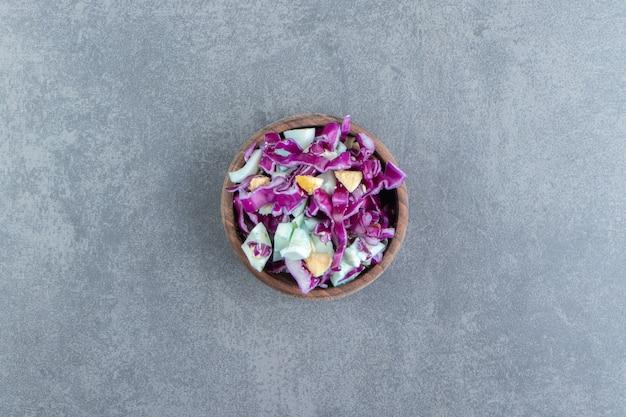 Sałatka ze świeżych warzyw w drewnianej misce.