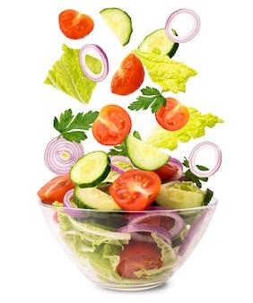 Sałatka ze świeżych warzyw. warzywa wpadające do miski z sałatką na białym, odizolowane.