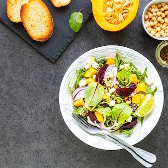 Sałatka ze świeżych warzyw z burakami, rukolą, czerwoną cebulą i szczawiem na białym talerzu z dynią, grzankami i ciecierzycą
