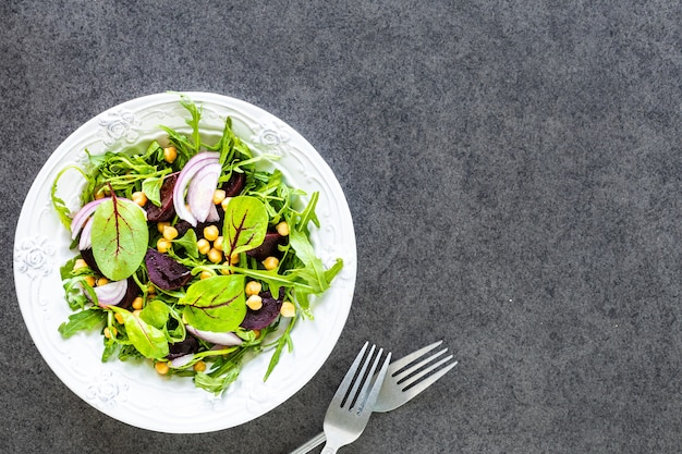 Sałatka ze świeżych warzyw z burakami, rukolą, czerwoną cebulą i szczawiem na białym talerzu