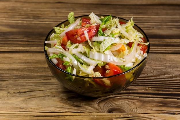 Sałatka ze świeżych warzyw z kapusty pekińskiej, pomidora, papryki i cebuli z oliwą lub olejem słonecznikowym na drewnianym stole. zdrowe jedzenie