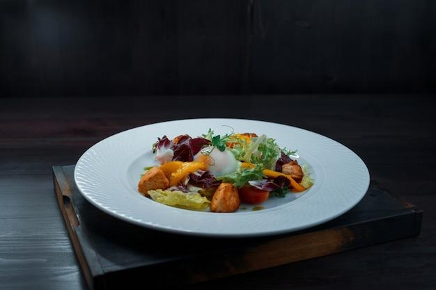 Sałatka ze świeżych warzyw z liśćmi zielonej sałaty z żółtą papryką z kawałkami smażonej czerwonej ryby i jajkiem w koszulce na białym talerzu w pomieszczeniu na stole w kawiarni.
