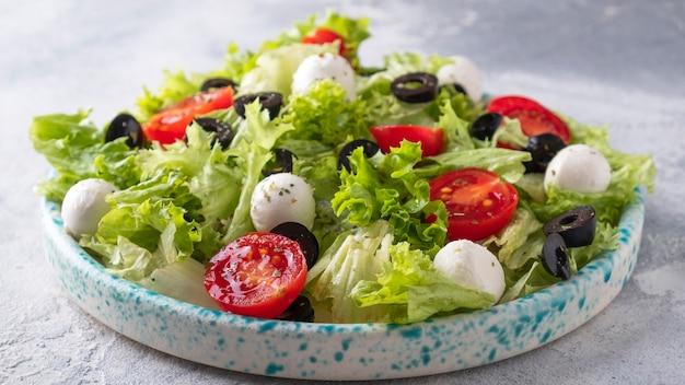Sałatka ze świeżych warzyw z pomidorami, mozzarellą i oliwkami.