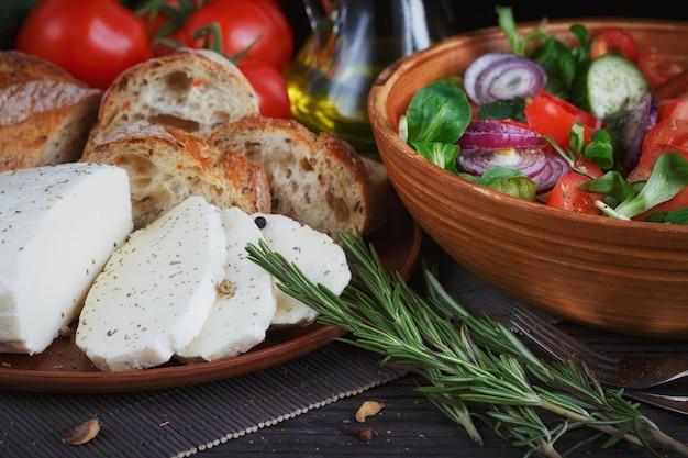 Sałatka ze świeżych warzyw z pomidorami, ogórkami i cebulą. podawany z serem, warzywami, oliwą i pieczywem