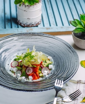 Sałatka ze świeżych warzyw z rzodkiewką, pomidorem, ogórkiem, kostkami sera feta, rukolą