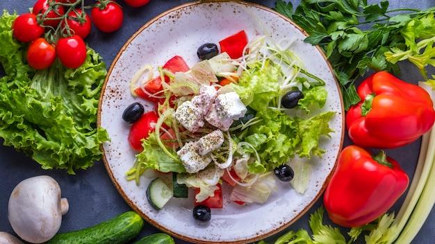 Sałatka ze świeżych warzyw z serem feta i czarnymi oliwkami. widok z góry