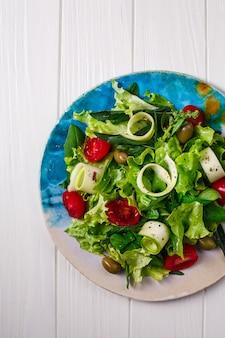 Sałatka ze świeżych warzyw z zieleniną i pomidorami.