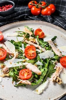 Sałatka ze świeżym kurczakiem z fetą, pomidorem, orzechami i warzywami. koncepcja zdrowej żywności. szara powierzchnia. widok z góry.