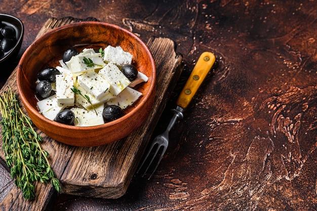 Sałatka ze świeżym serem feta, tymiankiem i oliwkami. ciemne tło. widok z góry. skopiuj miejsce.