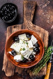 Sałatka ze świeżym serem feta, tymiankiem i oliwkami. ciemne tło. widok z góry.