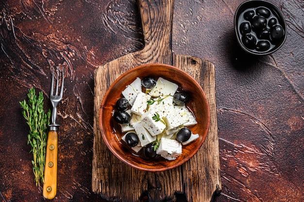 Sałatka ze świeżym serem feta, tymiankiem i oliwkami. ciemny stół. widok z góry.