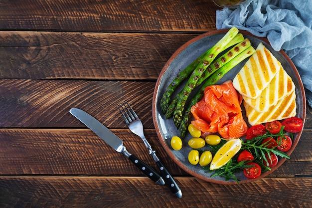 Sałatka ze szparagami, grillowanym serem halloumi, filetem z łososia, pomidorami, rukolą i zielonymi oliwkami. widok z góry