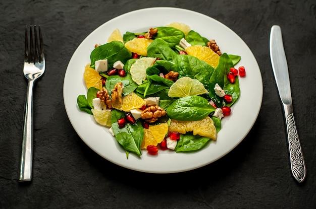 Sałatka ze szpinakiem, pomarańczy, cytryny, granatu, sera feto, orzecha włoskiego na białym talerzu na tle łupków, kamienia lub betonu