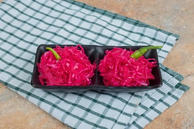 Sałatki z czerwonej kapusty kiszonej na czarnym talerzu z obrusem
