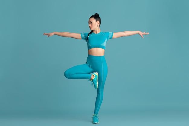 Saldo. piękna młoda lekkoatletka ćwicząca w studio, monochromatyczny niebieski portret
