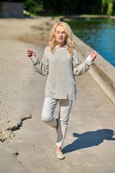 Saldo. spokojna kobieta w lekkich, swobodnych ubraniach z ramionami do boków uniosła jedną nogę, robiąc jogę na słonecznym brzegu morza