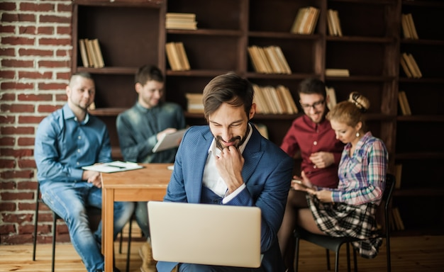 Sales manager z laptopem i zespołem biznesowym omawiający bieżące problemy firmy