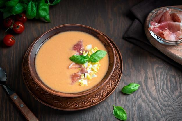 Salmorejo zupa pomidorowa na zimno udekorowana listkiem bazylii i gotowanym jajkiem podawana z jamonem i łyżką