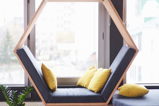 Salon biurowy wnętrze biurowca lub kawiarni, rozkładane krzesło w kształcie sześciokąta z poduszkami w pobliżu okna