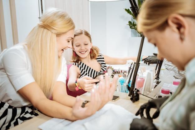 Salon dla gości. roześmiana matka i córka razem odwiedzają salon manicure