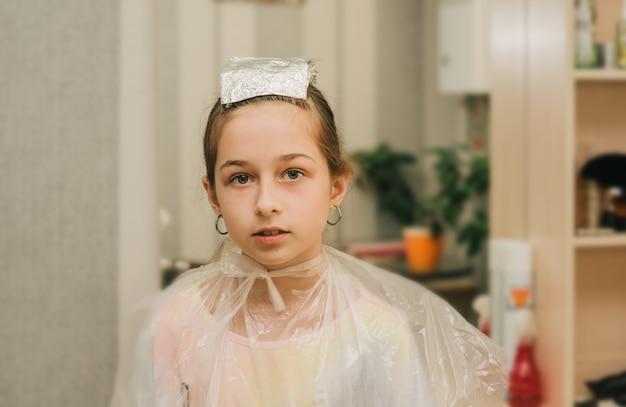 Salon fryzjerski co fryzury dla ślicznej dziewczynki. nastolatka ma rozjaśnioną grzywkę w salonie piękności. pomarańczowe grzywki. trend jasnych włosów.