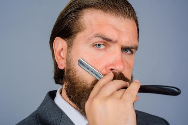 Salon fryzjerski dla mężczyzn fryzjer brodaty mężczyzna z brzytwą przystojny brodaty mężczyzna z narzędziami fryzjerskimi
