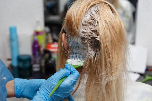 Salon fryzjerski. farbowanie włosów w trakcie. kobieta farbuje włosy.