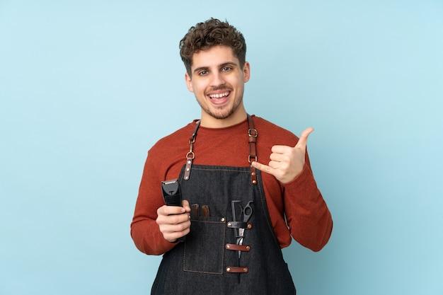 Salon fryzjerski kaukaski mężczyzna na białym tle na niebiesko dokonywanie gest telefonu