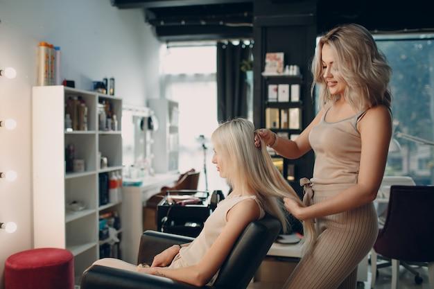 Salon fryzjerski kobieta dokonywanie przedłużania włosów do młodej kobiety z blond włosami w gabinecie kosmetycznym. profesjonalne przedłużanie włosów.