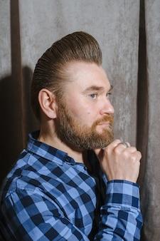 Salon fryzjerski, mężczyzna z fryzjerem na brodę. piękne włosy i pielęgnacja, salon fryzjerski dla mężczyzn. profesjonalna fryzura, retro fryzura i stylizacja. obsługa klienta.
