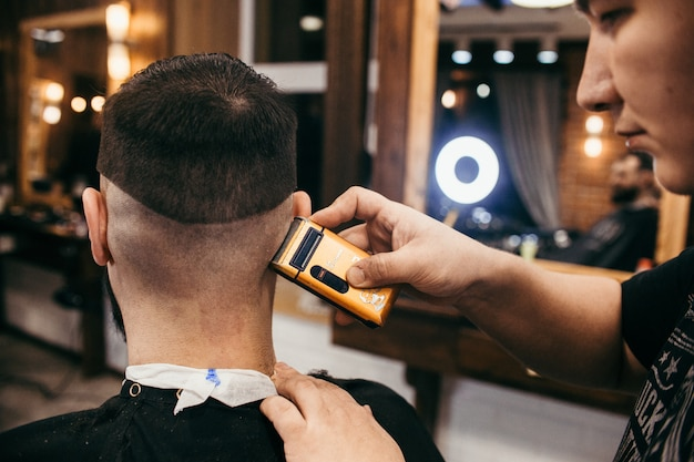 Salon fryzjerski, mężczyzna z fryzjerem na brodę. profesjonalna fryzura, retro fryzura i stylizacja. piękne włosy i pielęgnacja, salon fryzjerski dla mężczyzn. obsługa klienta.