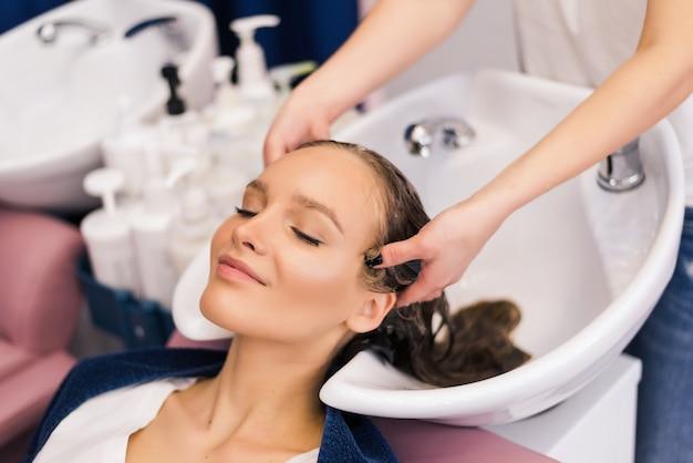 Salon fryzjerski mycie włosów klientki kobieta pod prysznicem w salonie stosując odżywkę szamponową na włosy na głowie