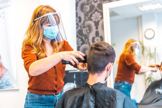 Salon fryzjerski, pandemia wirusa koronawirusa, covid-19. środki bezpieczeństwa, maska na twarz, ekran ochronny, dystans społeczny. bezpieczna praca, obcinanie włosów młodego mężczyzny po kwarantannie