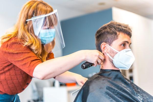 Salon fryzjerski, pandemia wirusa koronawirusa, covid-19. środki bezpieczeństwa, maska na twarz, ekran ochronny, dystans społeczny. bezpiecznie pracuje na otwarciu z młodym mężczyzną