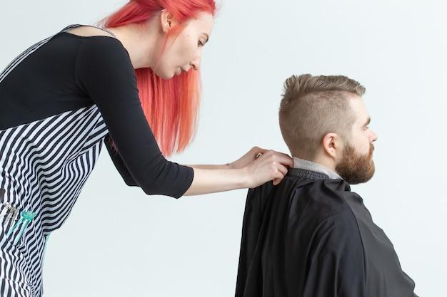 Salon fryzjerski, stylista i fryzjer koncepcja - fryzjerka kobieta tnie mężczyznę