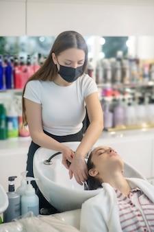 Salon fryzjerski. stylista włosów myje włosy klientowi w salonie fryzjerskim