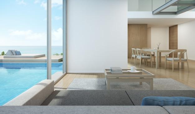 Salon i jadalnia z widokiem na morze w nowoczesnym domu przy basenie.