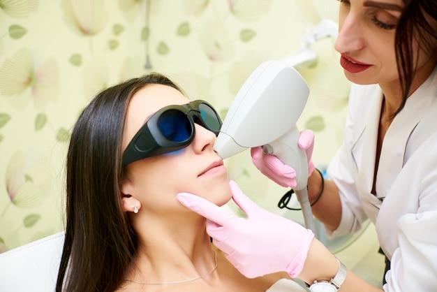 Salon kosmetyczny, laserowe usuwanie włosów, lekarz i pacjent