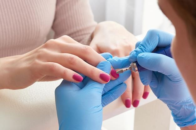 Salon kosmetyczny, manicure, lakierowanie paznokci. profesjonalny manicure sprzętowy na maszynie elektrycznej w gabinecie kosmetycznym. mistrz używa elektrycznej maszyny do usuwania lakieru z rąk podczas manicure