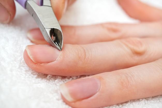 Salon kosmetyczny. proces manicure w salonie kosmetycznym lub w domu. zbliżenie kobiecej dłoni ze zdrowych naturalnych paznokci uzyskiwanie procedury pielęgnacji paznokci. zbliżenie dłoni do usuwania skórek z profesjonalnym narzędziem do paznokci.